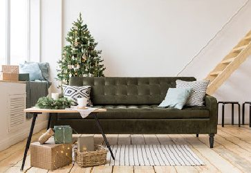 a green couch in a tidy holiday room